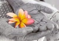 Foto em preto e branco com as mãos de uma senhora idosa segurando uma flor de orquidea colorida